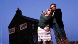 Two figures in front of local shop from BBC Archives